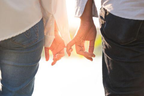 Wann hilft eine Beziehungspause? Ein Pärchen hält sich nur noch an den kleinen Fingern fest