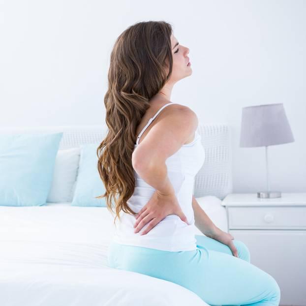Fibromyalgie: Frau sitzt mit Schmerzen auf dem Bett
