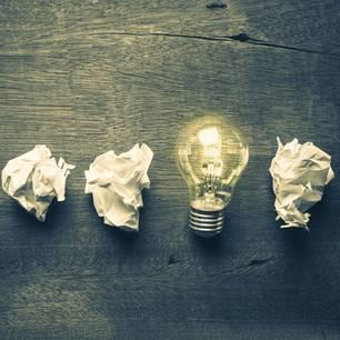 Lernmethoden - eine Übersicht: Zerknülltes Papier nebeneinander, dazwischen eine leuchtende Glühbirne