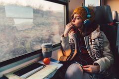 Frau sitzt in Bahn, hört Musik und schaut aus dem Fenster