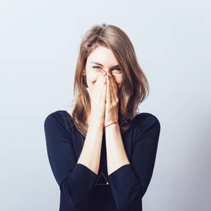 Gründe, warum man öfter fluchen sollte: junge Frau hält sich die Hände vor den Mund