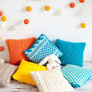Kissen häkeln: Ideen und Anleitungen: Viele gehäkelte Kissenhüllen auf dem Boden, darüber hängt eine bunte Lichterkette