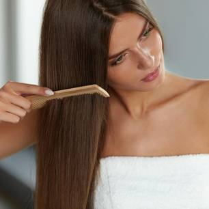 Keinen Scheitel ziehen: Frau kämmt ihre Haare