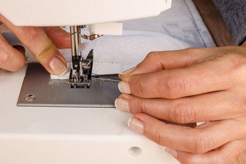 Tischdecke nähen ohne Schnittmuster: Frau näht einen Saum mit der Nähmaschine