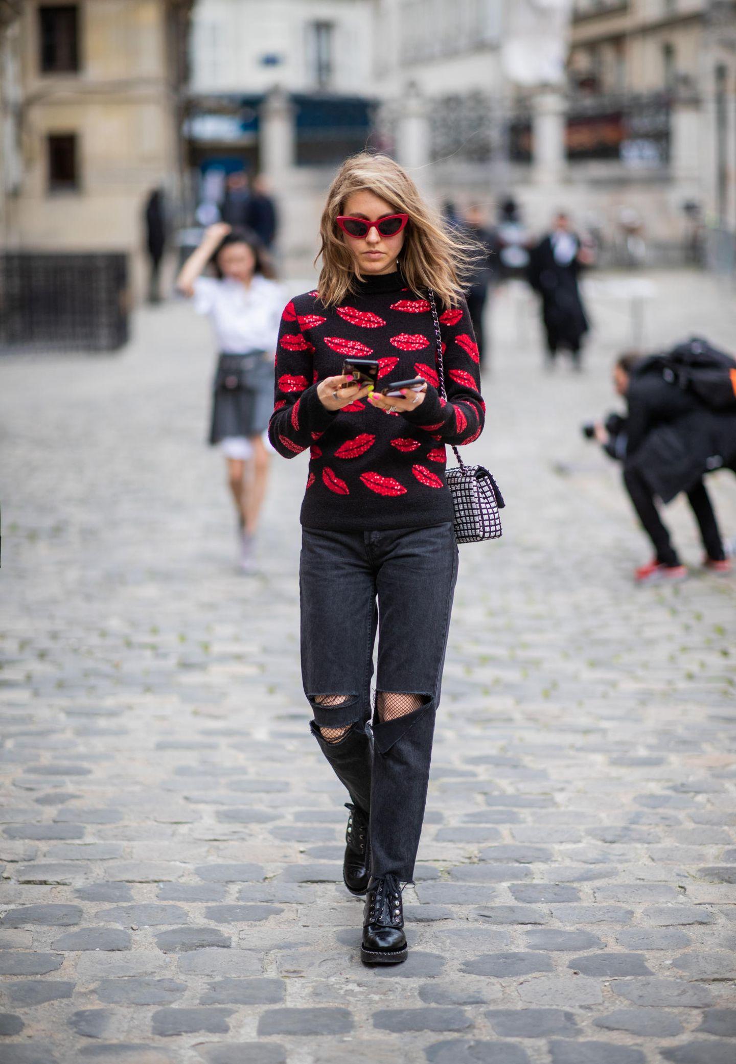 Outfits, die wir zur Arbeit tragen würden: Frau mit schwarzer Jeans und Pullover mit Kussmund