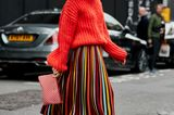 Outfits, die wir zur Arbeit anziehen: Frau mit Midirock und rotem Pullover