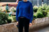 Outfits, die wir zur Arbeit anziehen: Frau mit blauem Pullover und schwarzer Hose