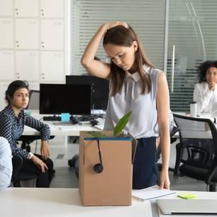 Betriebsbedingte Kündigung: Frau packt Arbeitssachen zusammen vor Abschied