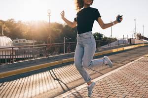 Ribcage Jeans: Frau springt vor Freude in die Höhe