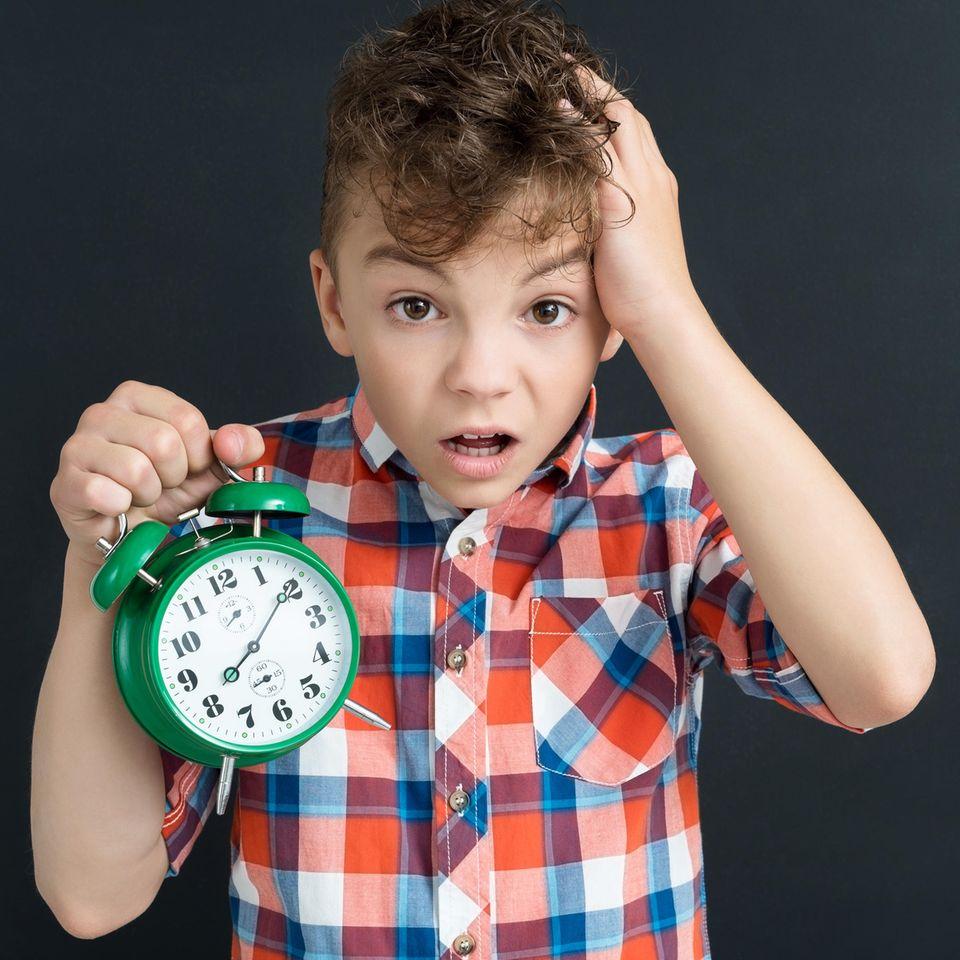 Junge hält analoge Uhr in die Luft und fasst sich an den Kopf