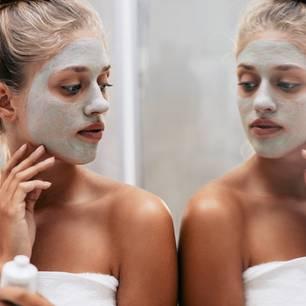 Hautprobleme durch Stress: Frau schaut sich ihr Gesicht im Spiegel an