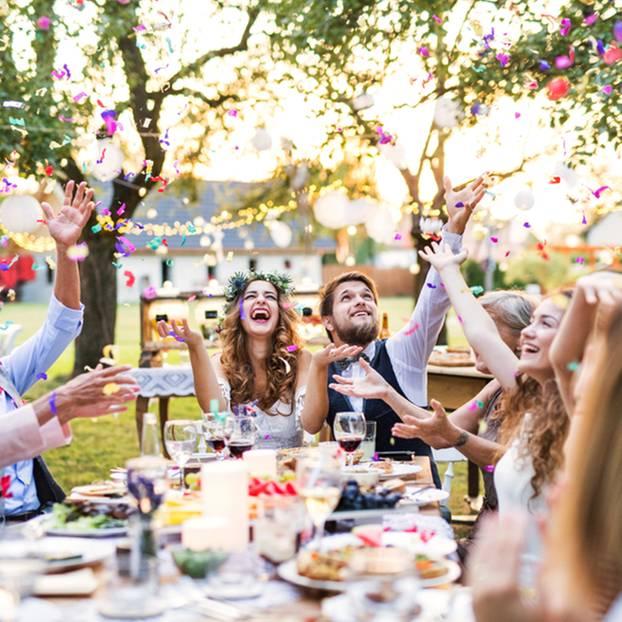 Gartenhochzeit - Tipps und Ideen für eure Traumhochzeit: Brautpaar sitzt mit Gästen im Garten am Tisch und werfen Konfetti