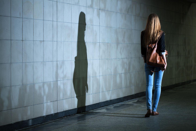 Böse Menschen: Eine Frau geht durch einen U-Bahn-Schacht und wirft einen dunklen Schatten an die Wand