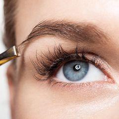 Frau zupft Augenbrauen