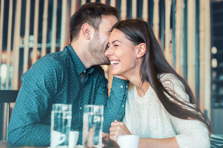 Schlechte Anmachsprüche: Ein Mann flüstert einer Frau was ins Ohr und sie lacht