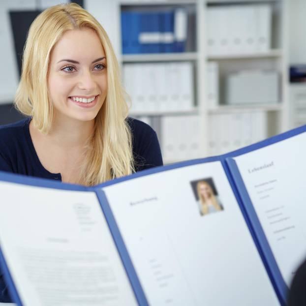 Anlagen in der Bewerbung: Personaler schaut sich Zeugnisse an