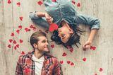 Eheversprechen: praktische Tipps und Beispiele: Pärchen liegt auf dem Boden und sieht sich an, um sie herum rote Papierherzen