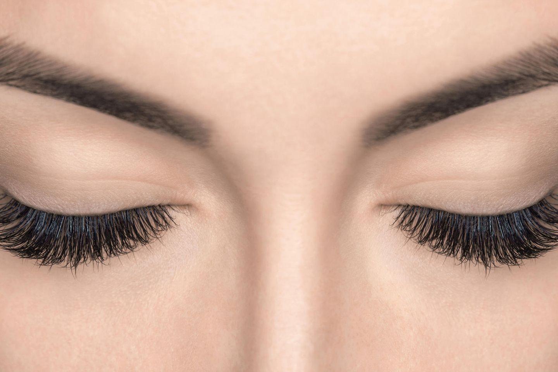 Wachsen Wimpern nach? Frau mit vollen, langen Wimpern und geschlossenen Augen