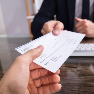 Abfindung versteuern: Mitarbeiter bekommt Scheck