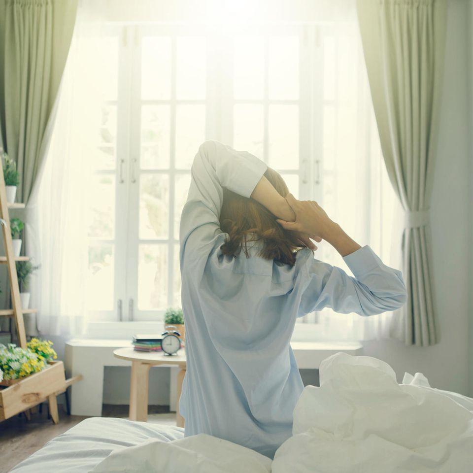 Studie: Eine Frau reckt sich auf dem Bett