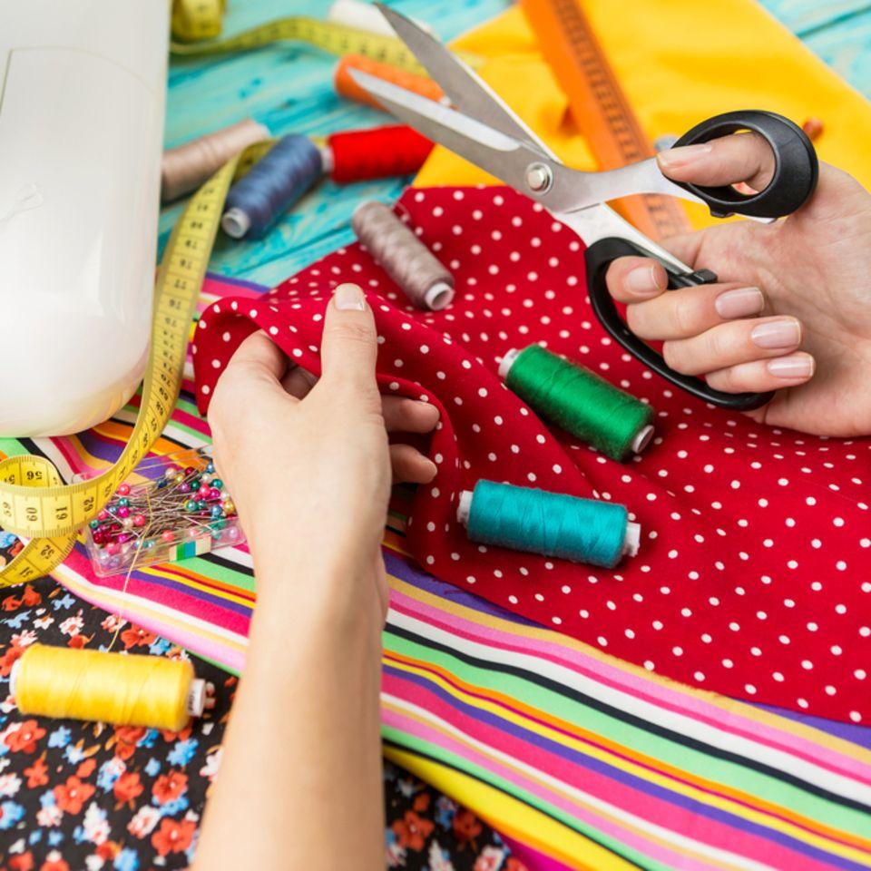 Wickeltasche nähen: Anleitung für Anfänger: Nähmaschine und viele Stoffe liegen auf einem Tisch, Frau hält Schere in der Hand