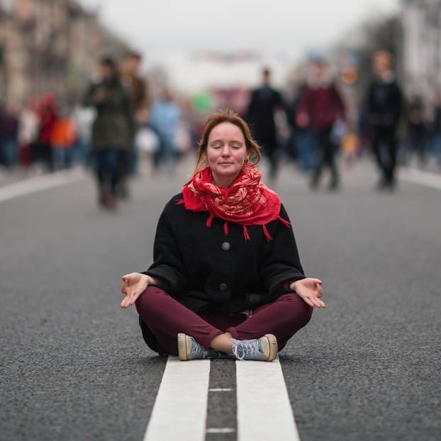 Genervt von anderen? Eine Frau meditiert auf der Straße