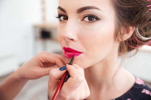 Braune Augen schminken: Frau bekommt pinke Lippen geschminkt