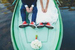 5 besondere Hochzeitslocations: Brautpaar sitzt auf dem Bug eines Bootes, der Blumenstrauß liegt vor den beiden