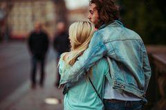 Beziehungsphasen: Ein Pärchen Arm in Arm von hinten