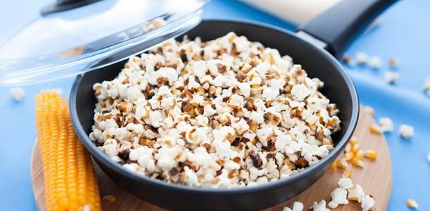 Popcorn selber machen: So leicht geht das Rezept: Pfanne gefüllt mit Popcorn steht auf einem Brett, ein Maiskolben liegt daneben