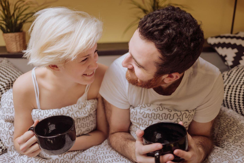 Woran erkennen Psychologen eine gesunde Beziehung? Ein Pärchen liegt mit Kaffeetassen im Bett und guckt sich fröhlich an