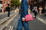 Traut euch! Ein Boilersuit aus Jeans sieht mega aus, pinkfarbene Accessoires machen ihn feminin.