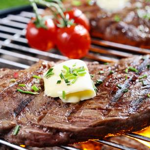 Grillbutter: 5 leckere Varianten: Fleisch mit Butter oben drauf auf dem Grill, daneben lieben drei Tomaten