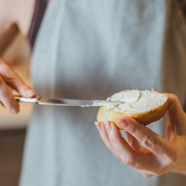 Frischkäse in der Schwangerschaft: Frau streicht Frischkäse auf ein Brot