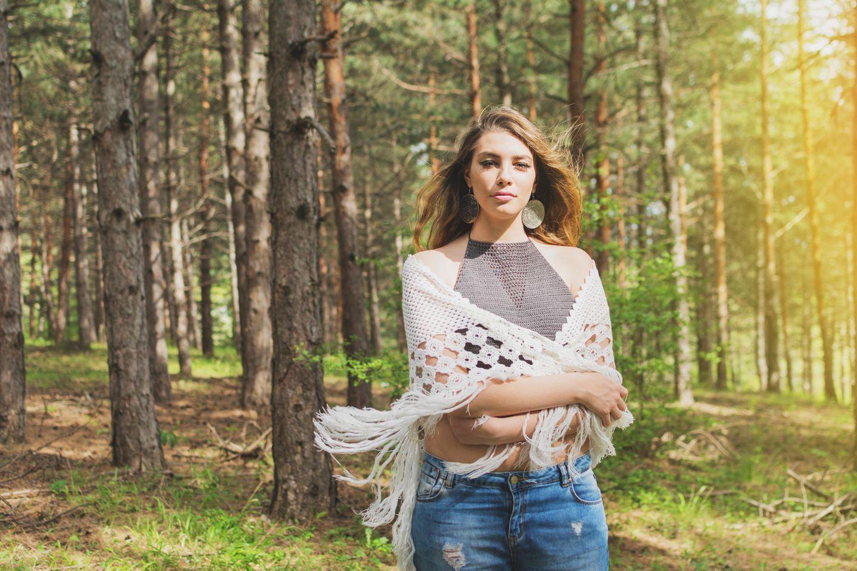 Stola häkeln: Anleitung und Ideen: Frau steht im Wald, ein Dreieckstuch um die Schultern gewickelt