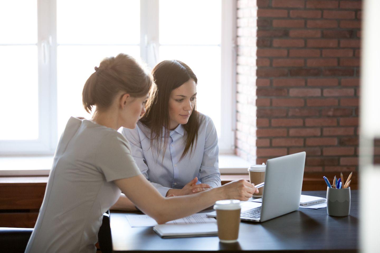 Rückkehr nach Krankheit: Zwei Frauen sitzen am Schreibtisch vorm Laptop