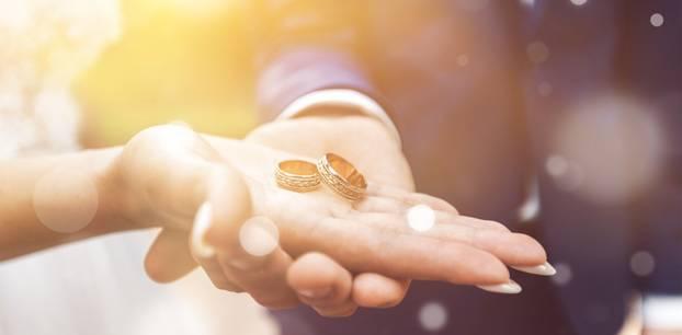 Hochzeitsquiz: Wann gibt's Kupfer, Silber, Gold? Brautpaar hält Eheringe in den Händen
