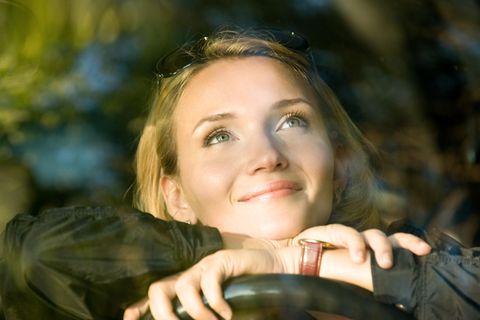 Gedanken-Trick für gute Laune: Eine fröhliche Frau schaut nachdenklich nach oben