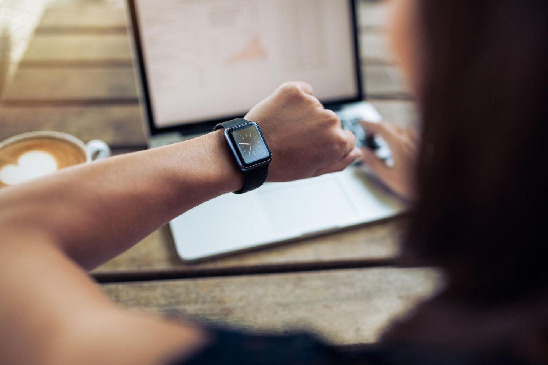 Überstunden auszahlen: Mitarbeiterin schaut auf die Uhr