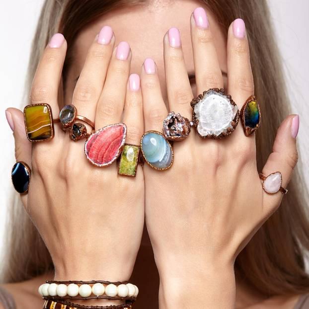 Ballerina Nails: Frau mit roséfarbenen Fingernägeln und Ringen