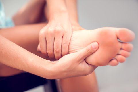 Fersensporn: Ursache und Behandlung: Frau umfasst Ferse und Fußsohle mit den Händen vor Schmerzen