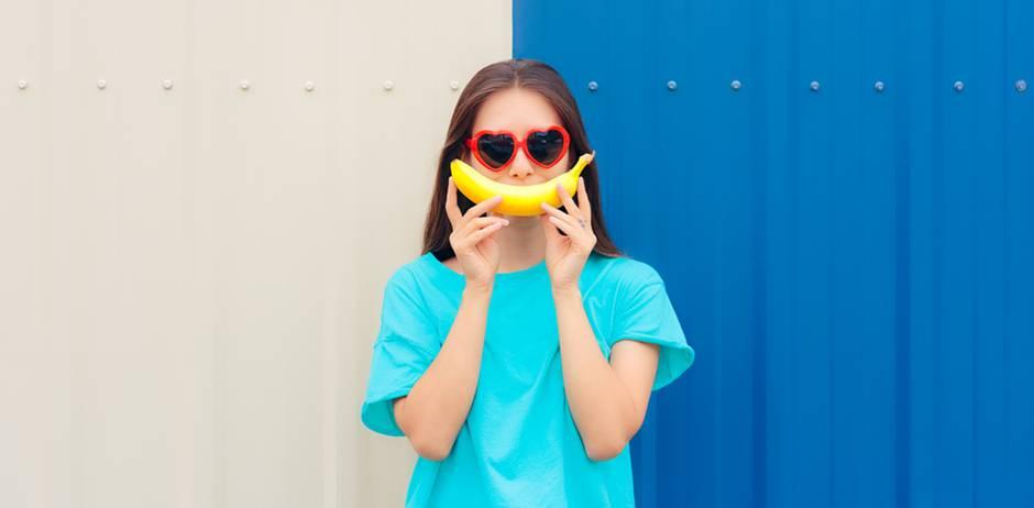 Gute-Laune-Essen: Frau mit Bananen-Lächeln vor blauer Wand