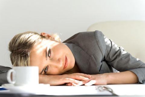 Vertrauensarbeitszeit: Mitarbeiterin legt Kopf auf Schreibtisch
