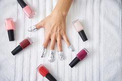 Shellac entfernen: Frau mit Nagellack und Alufolie auf den Fingernägeln beim Shellac entfernen