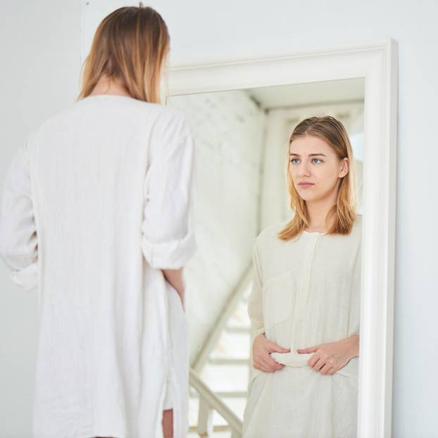 Woran merke ich, dass andere mein Leben bestimmen? Eine zweifelnde Frau vor dem Spiegel