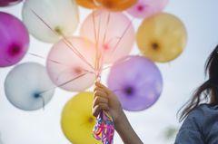 In welchem Alter ist das Selbstvertrauen am größten? Eine Frau mit bunten Luftballons