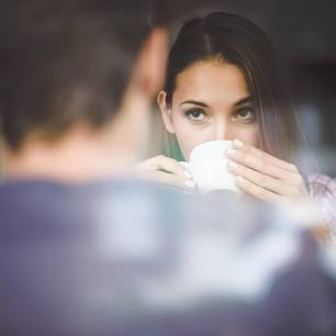 Geheimnisse in der Beziehung: Eine Frau schaut ihren Freund geheimnisvoll an