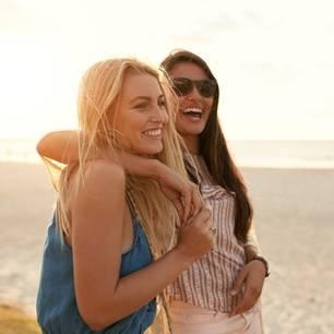 Mädelsurlaub: 5 fantastische Ideen: zwei Frauen lachend am Strand