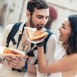 Was sollte man nicht mit dem Partner teilen? Eine Frau lässt ihren Freund von ihrer Pizza abbeißen