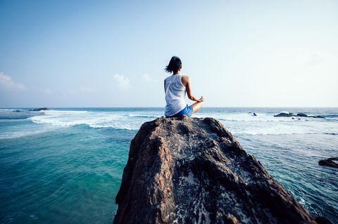 Mentales Training: Frau meditiert auf Felsen am Meer